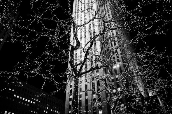 "view of Rockefeller Center ""The Rock"" through a tree with christmas lights"