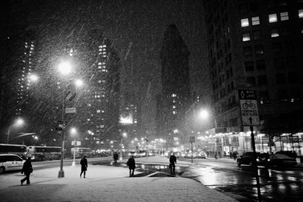 pedestrians during a Blizzard crsossing the street in front of the Flatiron building