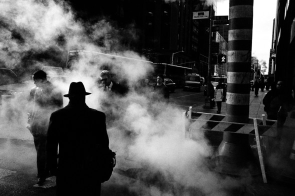 silhouette with hat walking into smoke on an avenue in manhattan