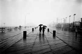 A couple with umbrellas walking down the boardwalk in coney island, brooklyn