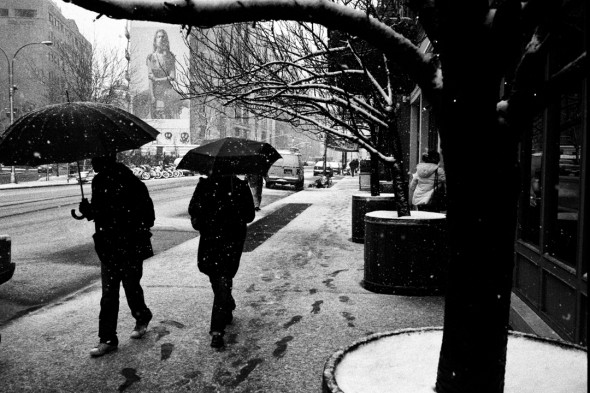 Two people covering with their umbrellas during a blizzard, nyc